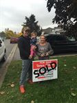 Family with child with sold sign